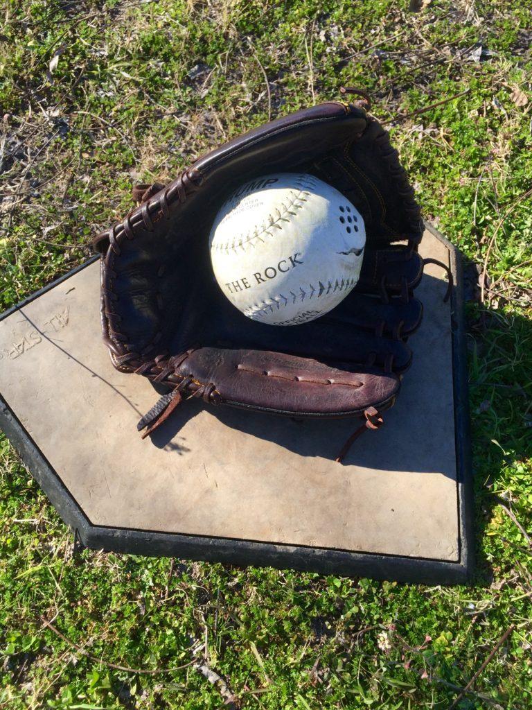 A beep baseball nestled in a baseball glove sits on home plate.