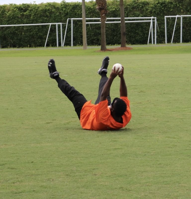 A player dressed in bright orange holds the ball high above his body while on his back.
