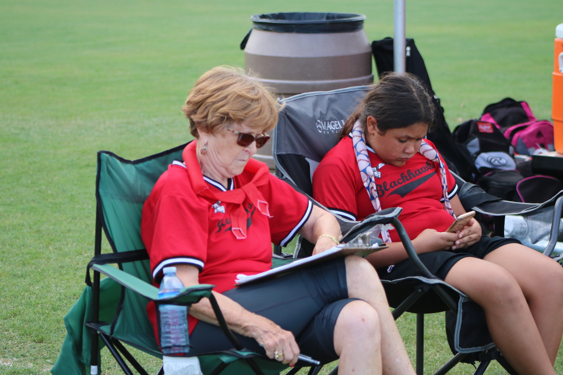 Two Austin Blackhawks volunteers sit on the sidelines.