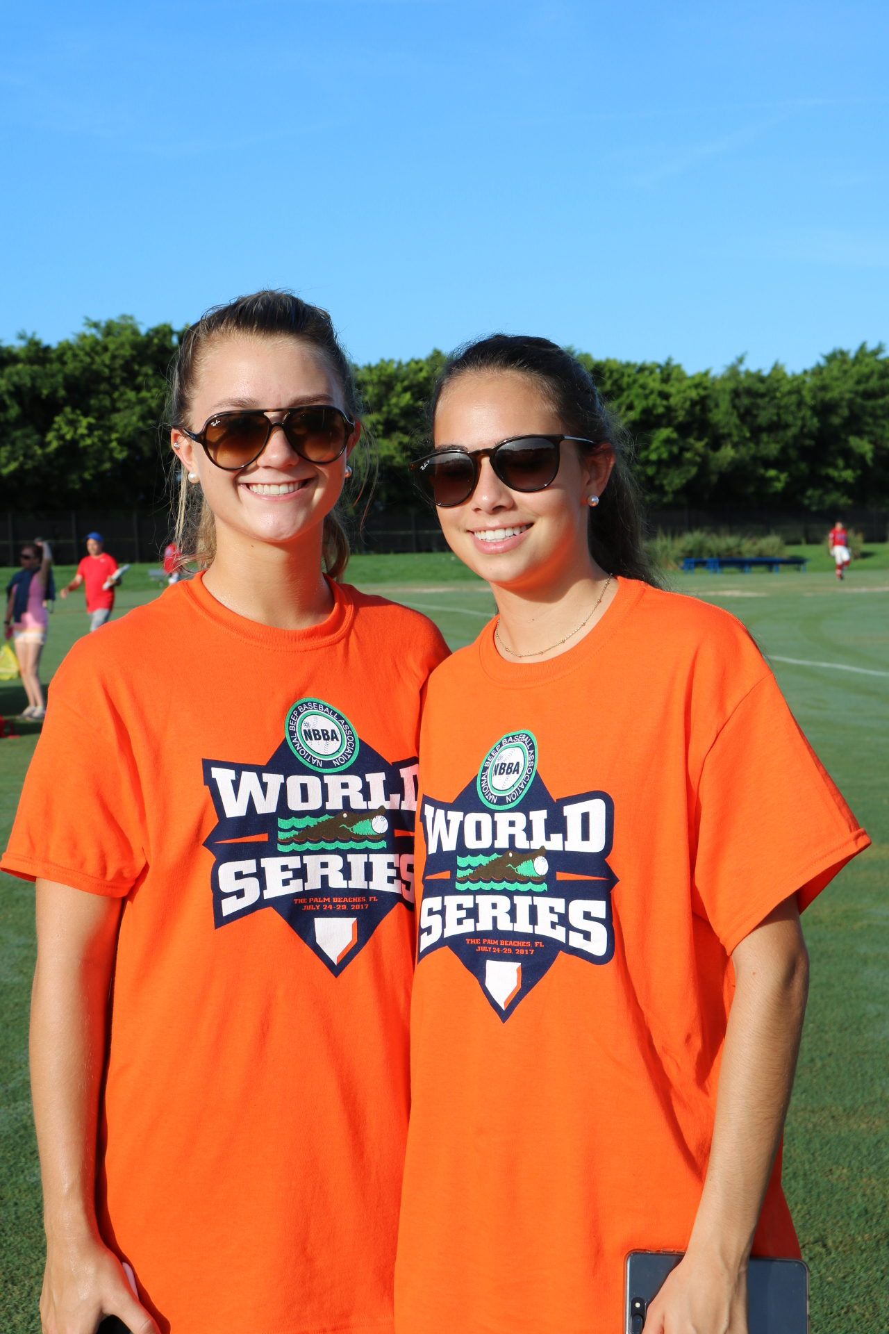 Two World Series volunteers smile for the camera from the sidelines.
