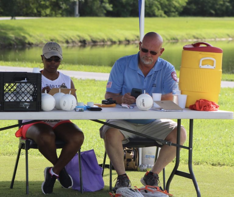 A scorekeeper and umpire sit behind a table.