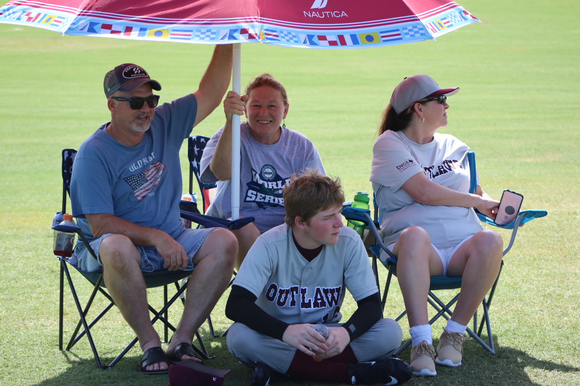 A BCS Outlaw's player rests in the shade of an umbrella held up by a few fans.