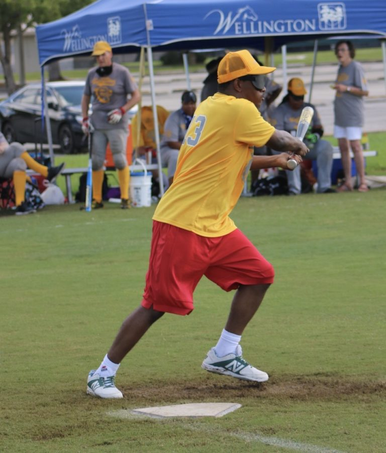 A player dressed in yellow swings the bat to the side as he launches off of home plate.