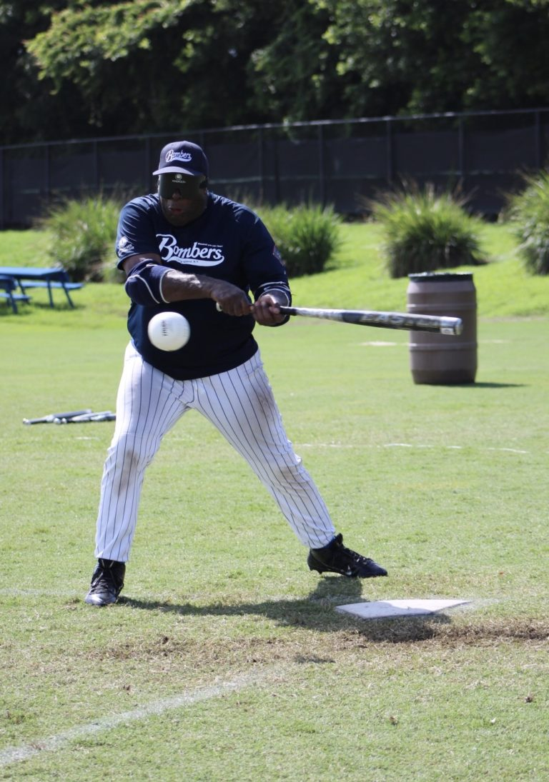 A Long Island Bombers player swings the bat as a ball flies towards him.