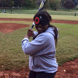Lakisha smiles while standing in a batting stance.