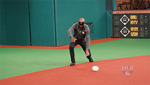 Harold Reynolds crouches to scoop a bounding grounder.