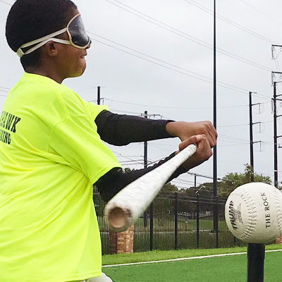 A blindfolded youth athlete nearly makes contact as she swings a bat at a ball on a tee.