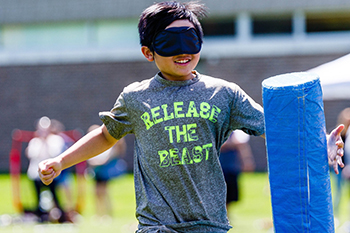 A blindfolded youth player runs to tag a padded base structure.